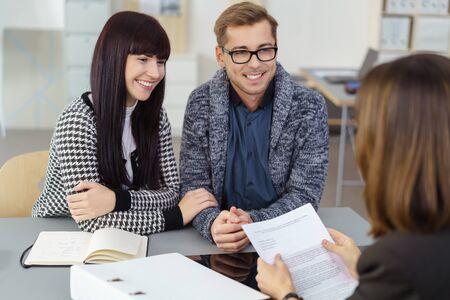 agente comercial: joven pareja casada en una reunión con un corredor de inversiones o agente discusión de un documento con ella con sonrisas felices