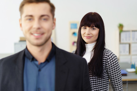 foreground focus: Smiling attractive businesswoman with a male colleague in the foreground standing in a corporate office with focus to her