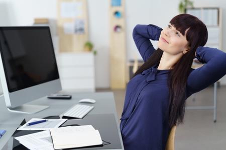 ejecutivo en oficina: El éxito de negocios relajado en su silla en la oficina con las manos entrelazadas detrás de la cabeza y una sonrisa soñadora de satisfacción Foto de archivo
