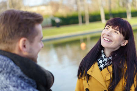 mate married: Happy young woman enjoying a day outdoors with her husband looking up into the air with a vivacious smile as they stand beside a canal Stock Photo