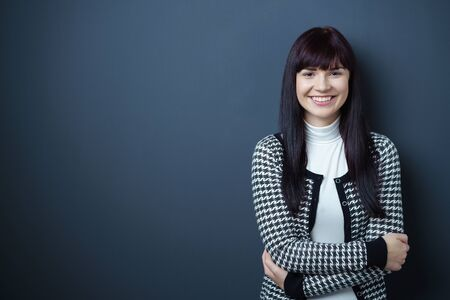 dark haired woman: Smiling confident attractive young woman with a gorgeous beaming wide smile posing with folded arms against a dark background with copy space Stock Photo