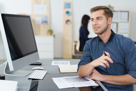 blue shirt: Handsome young businessman with a thoughtful expression sitting at his desk looking across at his blank computer monitor visible to the camera