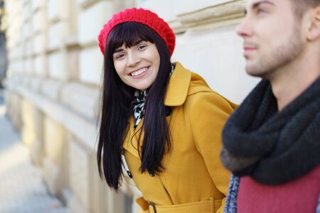 leaning forward: Gorgeous vivacious trendy young woman in a colorful red and yellow outfit standing with her boyfriend against an exterior wall leaning forward to smile at the camera Stock Photo