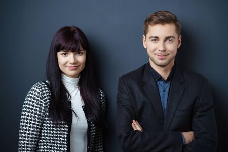 Smiling confident young business team with a stylish man and woman posing against a dark studio background looking at the camera, upper body Stock Photo
