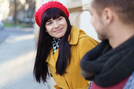 leaning forward: Happy young woman in colorful autumn fashion leaning forward with a lovely smile to look at a young man standing alongside her