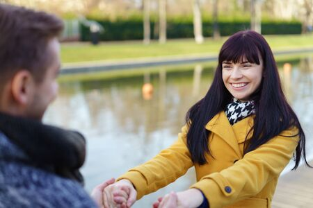 Happy pretty young woman in love holding the hands of her partner and leaning back with a beaming smile as they stand outdoors alongside a canal
