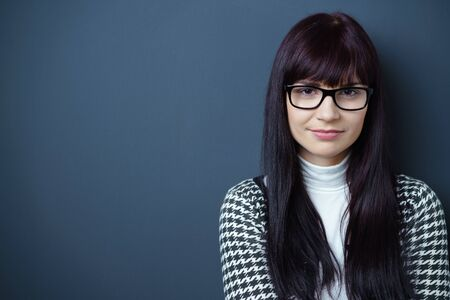 adult wall: Young adult woman with eyeglasses standing against blue wall