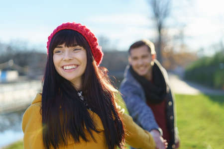 Trendy gorgeous young woman with a wide beaming smile holding the hand of her boyfriend behind as they enjoy a date outdoors in nature Stock Photo