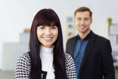 coworker: Happy confident business manageress or entrepreneur posing looking at the camera with a friendly smile with a male co-worker behind