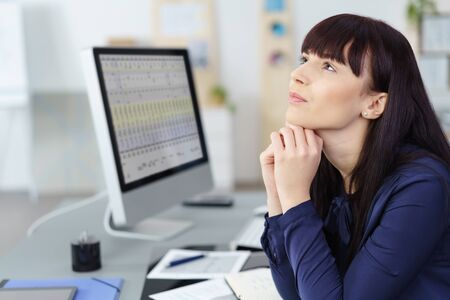 absorbed: Thoughtful businesswoman sitting at her desk in front of a spreadsheet on a desktop monitor staring up with a pensive expression, side view
