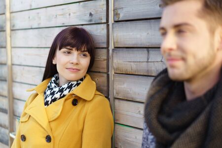 they are watching: Attractive young woman watching her husband with a serious thoughtful expression as they stand together outdoors leaning on a wooden wall Stock Photo