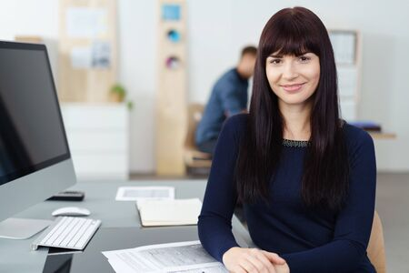 lovely businesswoman: Pretty friendly young businesswoman with a a lovely warm sincere smile sitting at her desk in the office looking at the camera