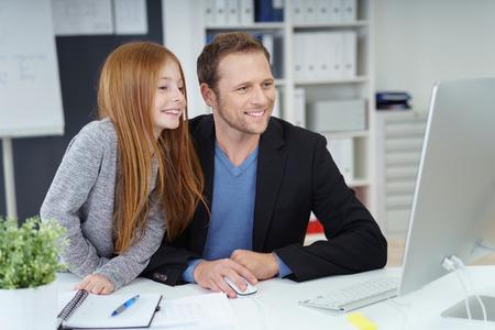 papa: Beau père assis à côté de la fille aux longs cheveux roux derrière le bureau, car ils utilisent un ordinateur et à l'étude Banque d'images