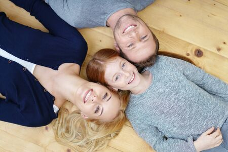wood flooring: Smiling happy family with a pretty young girl and her parents lying head to head on a wooden floor grinning up at the camera