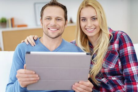 couple relaxing: Happy friendly attractive young couple relaxing together on a sofa at home with a tablet computer looking at the camera with warm smiles