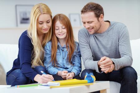 Glückliche Familie die Hausaufgaben zusammen, wie die Eltern ihre attraktive junge Rotschopf Tochter mit ihrer Klasse arbeiten auf dem Sofa zu Hause helfen
