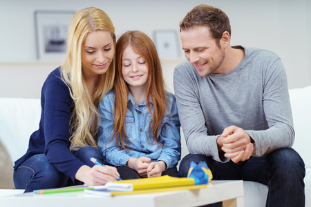 deberes: La familia feliz haciendo la tarea juntos como los padres a ayudar a su hija atractiva joven pelirroja con su trabajo de clase en el sof� en casa Foto de archivo