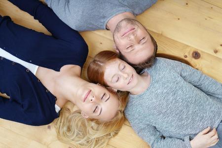 Молодая семья, расслабляющий голова к голове на деревянном полу в гостиной с закрытыми глазами в довольстве, вид сверху