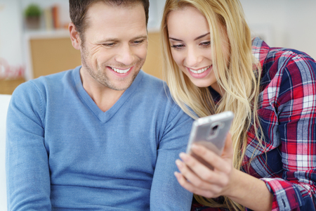 looking at: Young couple looking at the screen of a mobile phone together with happy smiles as they relax at home on the sofa