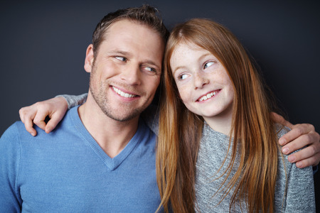 redhead girl: Handsome young Dad and his pretty redhead daughter giving each other teasing knowing looks, head and shoulders on dark background