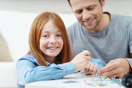 automobiles: Happy female red haired child working on electronic project with helpful father indoors