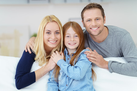 affectionate: Loving affectionate happy young family with a pretty little redhead daughter posing arm in arm on a comfortable sofa at home smiling at the camera