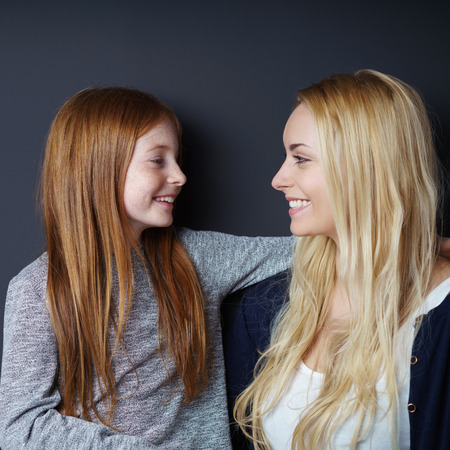 facing each other: Happy loving young mother and daughter posing facing each other smiling into each others eyes Stock Photo
