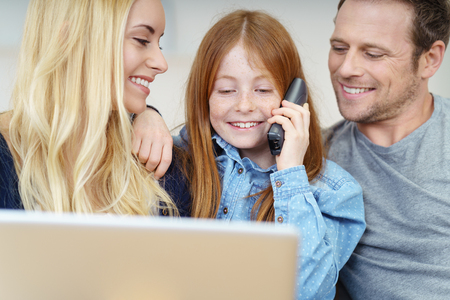 indulgent: Smiling little girl chatting on a phone to her friends as her indulgent parents look on with loving smiles Stock Photo
