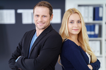 co operation: Confident successful business team of a man and woman standing back to back in the office with folded arms smiling at the camera