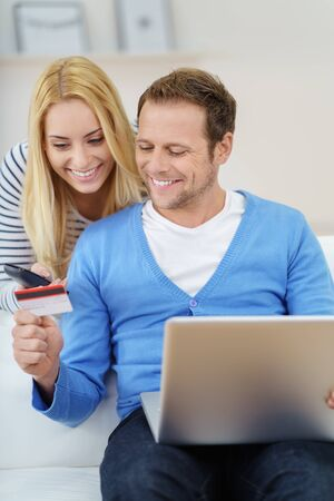 anticipating: Young couple anticipating buying online on credit using their laptop computer grinning happily as they eye their credit card