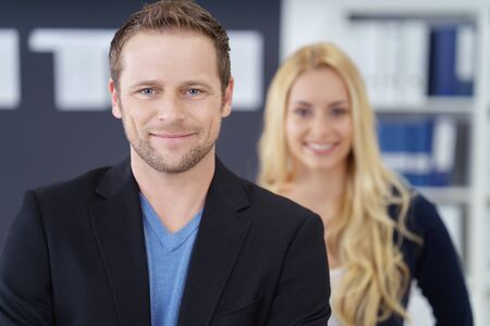 co operation: Grinning adult business man casual outfit in front of out of focus happy blond woman in office with shelf in background