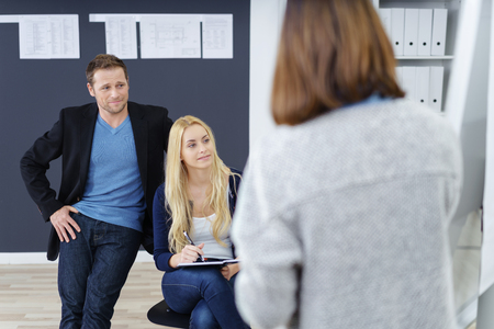 co operation: Businesswoman giving a presentation to two colleagues who are watching the flip chart attentively, focus over her shoulder to the co-workers Stock Photo