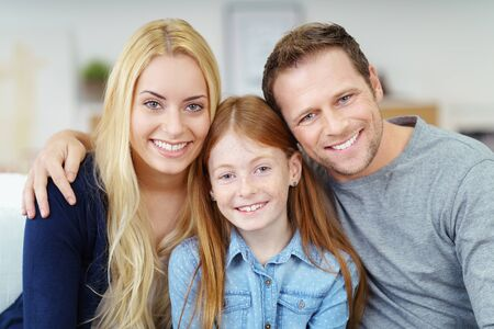 flanked: Attractive happy young family posing at home sitting close together on the sofa with a young pretty girl flanked by her parents all smiling at the camera