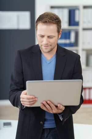 handheld computer: Handsome young businessman reading from a handheld tablet computer with a serious expression as he sits perched on the edge of a table in the office
