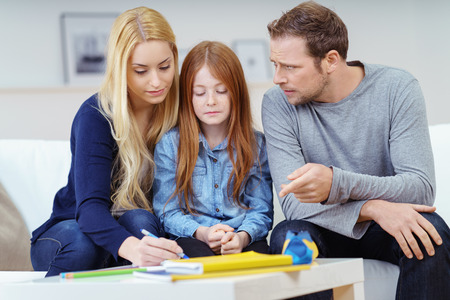 tarea escolar: Padres que ayudan a su hija con la tarea que tienen una discusión sobre las respuestas correctas ya que el niño se sienta en silencio escuchando