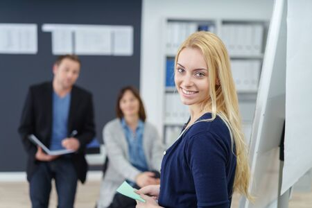 prompting: Attractive businesswoman giving a presentation standing in front of a flip chart with prompting reminder cards turning to smile at the camera Stock Photo