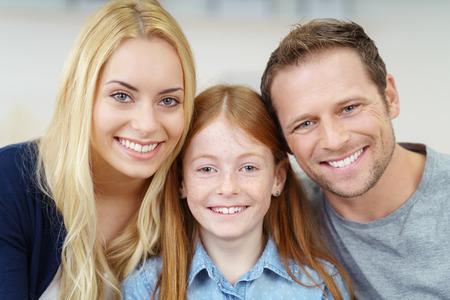 mom dad: retrato de una familia joven sonriente feliz con una chica pelirroja muy pequeña, flanqueada por sus padres posando juntos para la cámara Foto de archivo