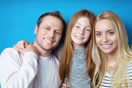 flanked: Happy attractive young family posing together with a pretty young redhead girl with a lovely smile flanked by her parents Stock Photo