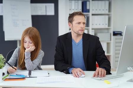 mujer sola: padre serio que se sienta junto a la hija con el pelo largo de color rojo detrás de la mesa, ya que utilizan un ordenador portátil y para estudiar