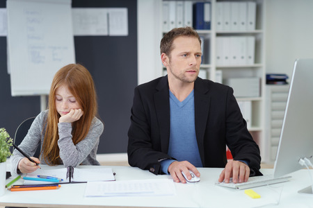 single family: Serious father sitting next to daughter with long red hair behind desk as they use a computer and notebook to study Stock Photo