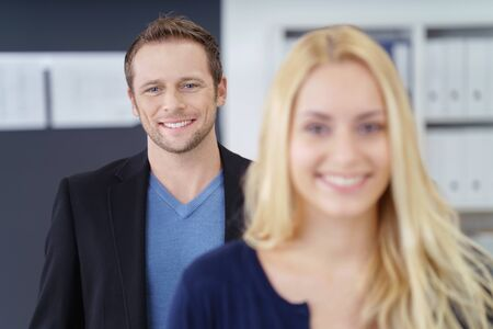 co operation: Grinning adult business man casual outfit standing closely behind out of focus happy blond woman in office with shelf in background