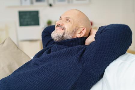 Gelukkig tevreden man van middelbare leeftijd met een sikje ontspannen thuis op de bank met zijn handen achter zijn hoofd lachend met plezier als hij kijkt omhoog in de lucht