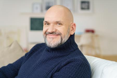 Atraktivní plešatý muž středního věku s kozí sedí relaxační na gauči doma při pohledu na fotoaparát s krásným širokým poutavé úsměv