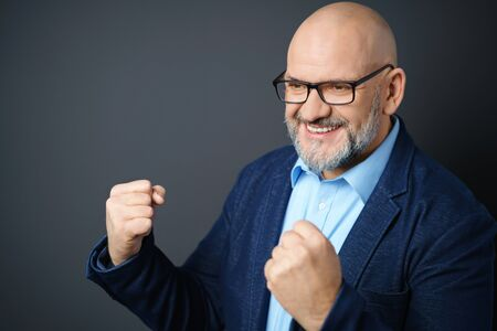 40 50: Jubilant businessman cheering his success raising both fists in the air as he smiles with satisfaction over a dark background with copy space Stock Photo