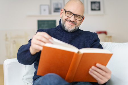 Middle-aged bald man with a goatee wearing glasses sitting on a comfortable couch enjoying a good book with a smile of pleasure Stockfoto