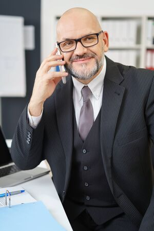 businessman phone: Waist Up of Mature Professional Businessman Wearing Suit and Eyeglasses Looking Confident and Smiling to the Side While Talking on Cell Phone at Desk in Modern Office Workplace Stock Photo