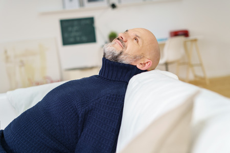 head tilted: Contented middle-aged man with a goatee beard relaxing at home on a comfortable sofa with his head tilted back staring into the air Stock Photo