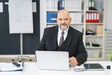 chief executive officers: Serious middle-aged business manager sitting at his desk in the office working on a laptop computer looking at the camera with a pensive expression Stock Photo
