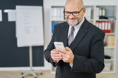 phone professional: Businessman reading a text message on his mobile phone with a pleased satisfied smile as he stands in the office