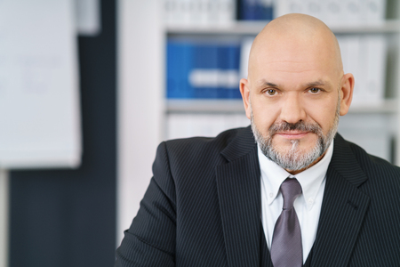 man 40 50: Confident middle aged handsome businessman with beard and bald head in suit and tie looking at camera Stock Photo